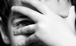 little boy covering face with hand one eye peeking