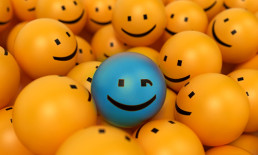 winking blue smiley surrounded by yellow smileys