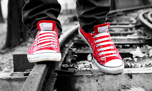 red and white shoes walking a black and white train track