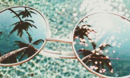 The Best Advice So Far: The 20-Minute Vacation - sunglasses reflecting palm trees over tropical waters