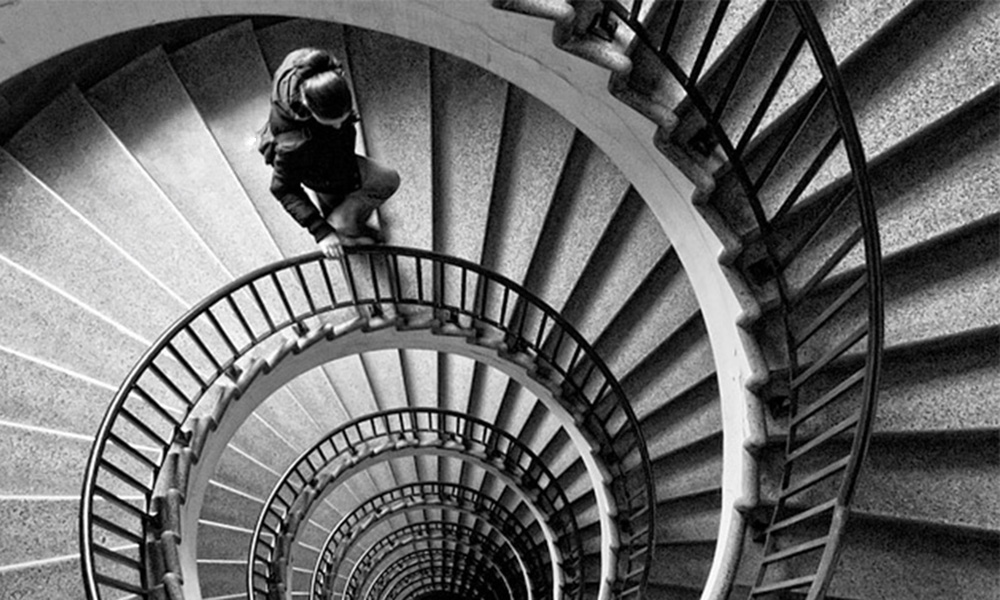 Black and white drawing of nondescript person walking down a flight of seemingly endless spiral stairs