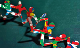 Paper dolls in a chain with world flags showing through
